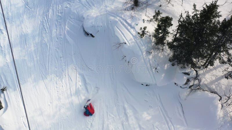 Flyg- b?sta sikt av en snowboarderridning fr?n pulversn?kullen som mycket ?r snabb och ner faller footage Hoppa f?r manboarder royaltyfri bild