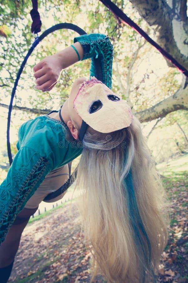 Flyg- beslagdans för kvinna i skog med maskeringen på framsida royaltyfria bilder