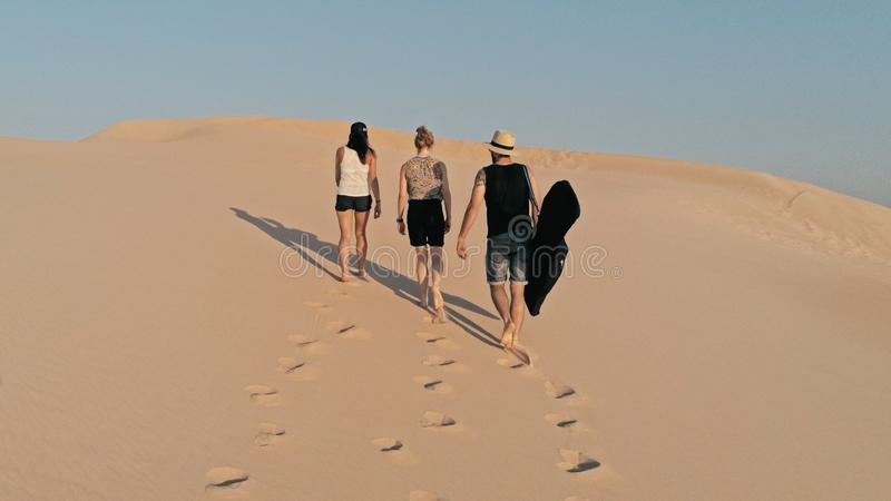 flyg- bild av ungdomarsom går upp på en sanddyn till maximumet i en härlig ökenmiljö arkivfoton