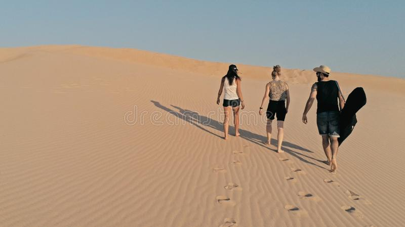 flyg- bild av ungdomarsom går upp på en sanddyn till maximumet i en härlig ökenmiljö royaltyfria foton