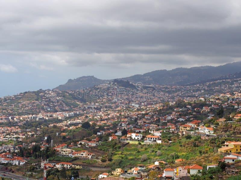 Flyg- cityscapesikt av utkanten av funchal i madeira med lantgårdar och hus med berg och molnig himmel i avståndet arkivbilder