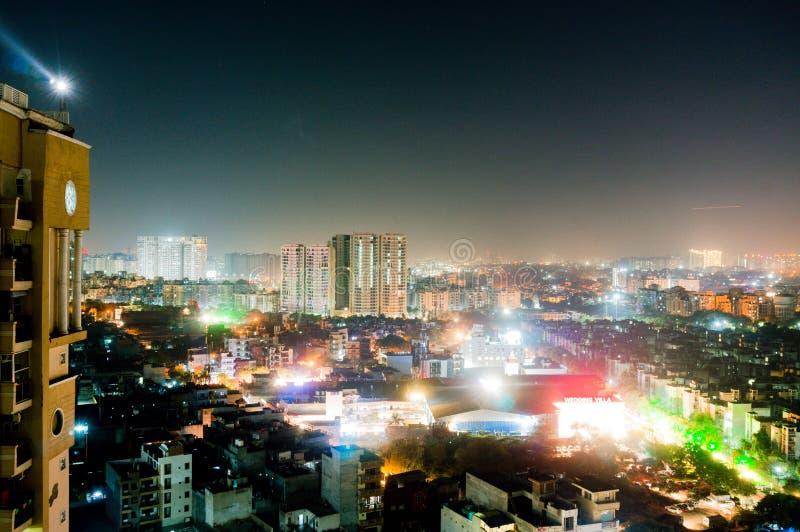 Flyg- cityscapeskott av Noida, delhi, grugaon på skymningnatten arkivfoto
