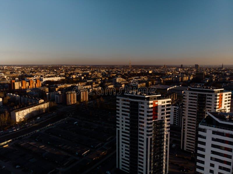 Flyg- dramatisk landskapsolnedgång med en sikt över skyskrapor i Riga, Lettland - det gamla stadcentret är synligt i royaltyfria bilder
