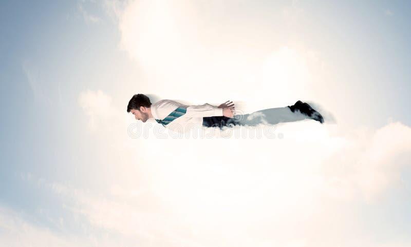 Flyg för affärsman som en superhero i moln på himlen arkivfoton