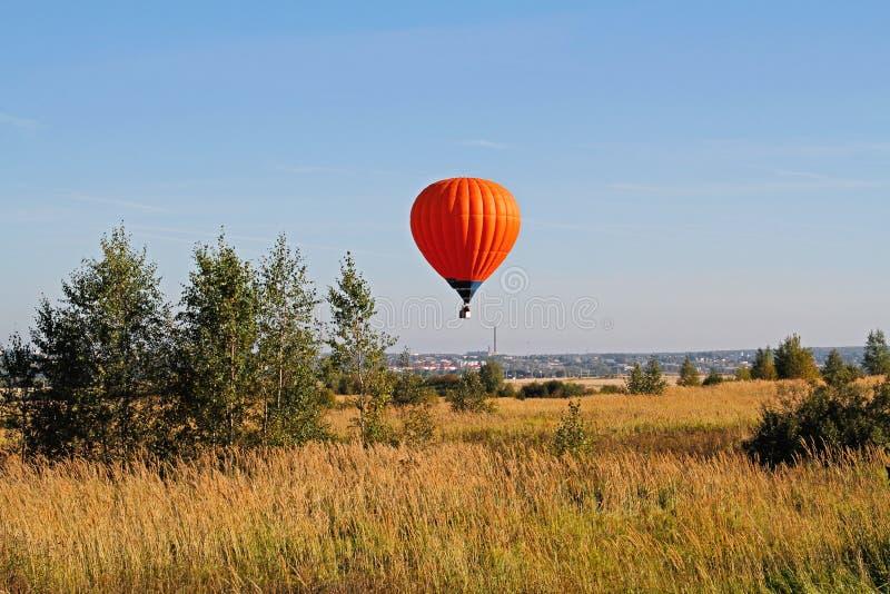 Flyg för ballong för varm luft över fältet med träd royaltyfria bilder