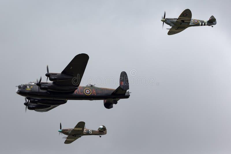 Flyg för Royal Air Force RAF Battle Of Britain Memorial flygAvro Lancaster bombplan PA474 i bildande med två kämpar arkivbild