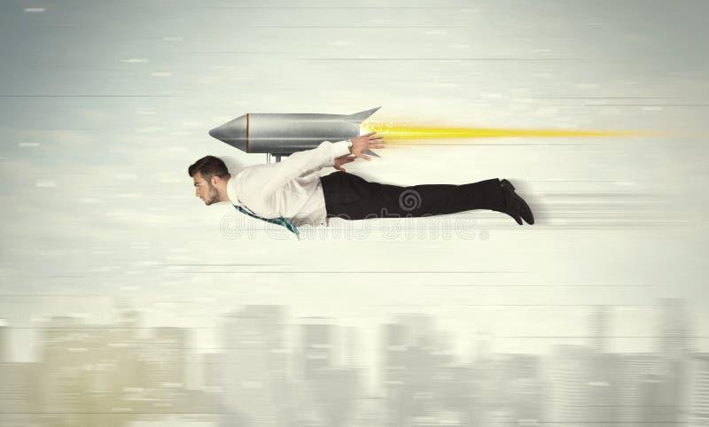 Flyg för Superheroaffärsman med strålpackeraket ovanför citen royaltyfri foto