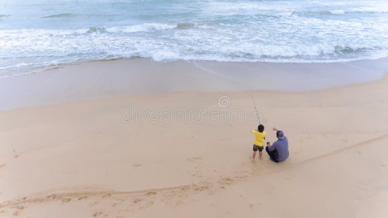 Flyg- fader- och sonfiske i havet surfar i tropisk strand in fotografering för bildbyråer