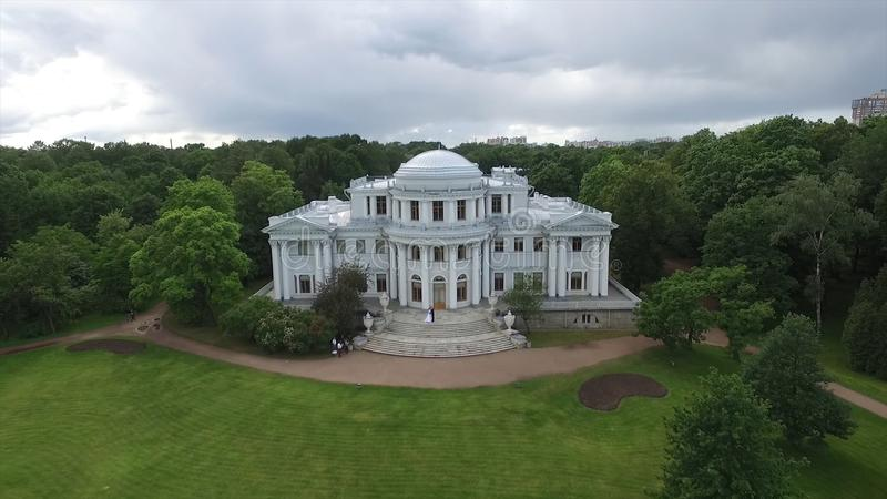 Flyg- granskning av bruden och brudgummen som dansar på slotten i trädgården Stor vit slott- eller slottsikt Flyga över royaltyfria foton
