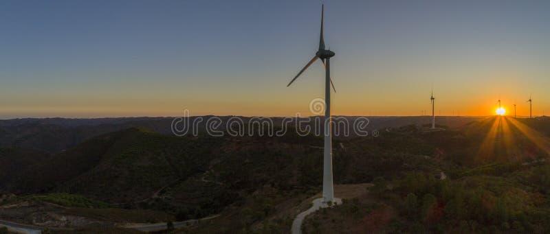 Flyg- kontur för turbiner för vindlantgård på solnedgången Ren förnybara energikällormakt som frambringar väderkvarnar arkivfoto