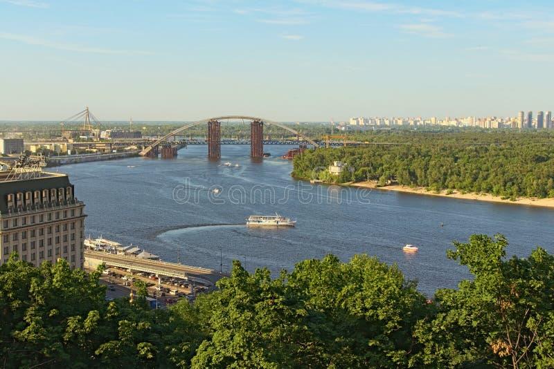 Flyg- landskapsikt av Kyiv på den soliga dagen för sommar Härlig Dnipro flod med broar och det Obolon området royaltyfri fotografi