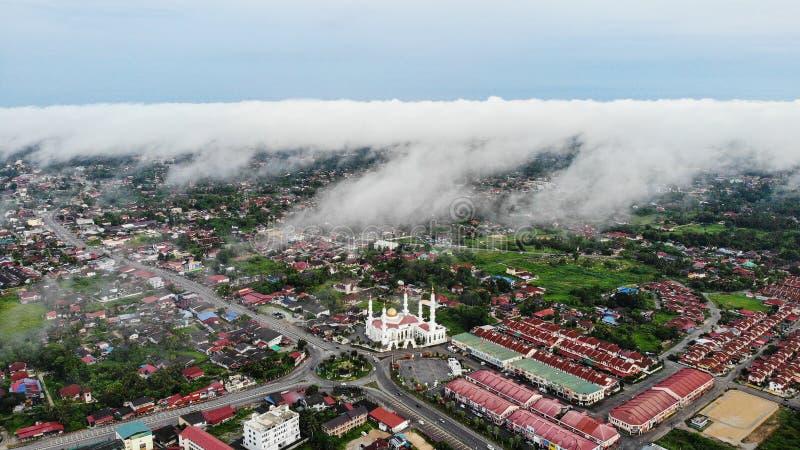Flyg- morgonsikt av al-Ismailimoskén som täckas med tjock dimma på Pasir Pekan Kelantan Malaysia fotografering för bildbyråer