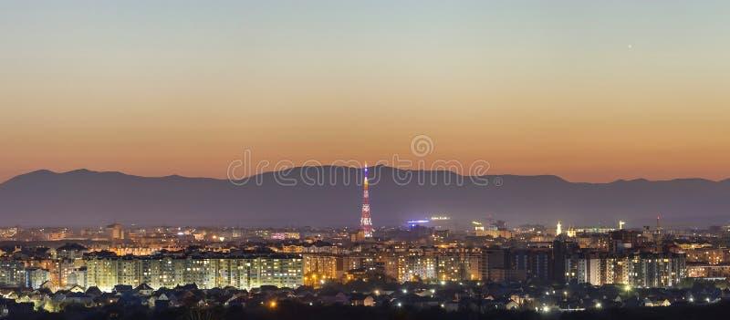 Flyg- nattsikt av den Ivano-Frankivsk staden, Ukraina Ljusa ljus av högväxta byggnader, det höga televisiontornet och förortstugo royaltyfria bilder