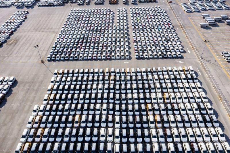 Flyg- nya bilar för bästa sikt uppställda i porten för den logistiska importexportaffären och trans. av skeppet i det öppna havet arkivfoton