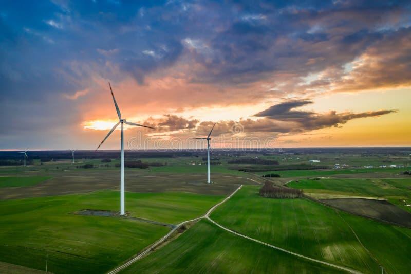 Flyg ovanför att bedöva vindturbiner på solnedgången fotografering för bildbyråer