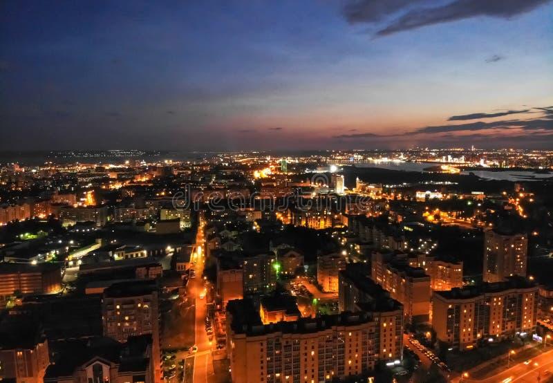 Flyg på surret ovanför nattstad med asfaltstadsvägar, bostads- byggnader och biltrafik på natten arkivbild
