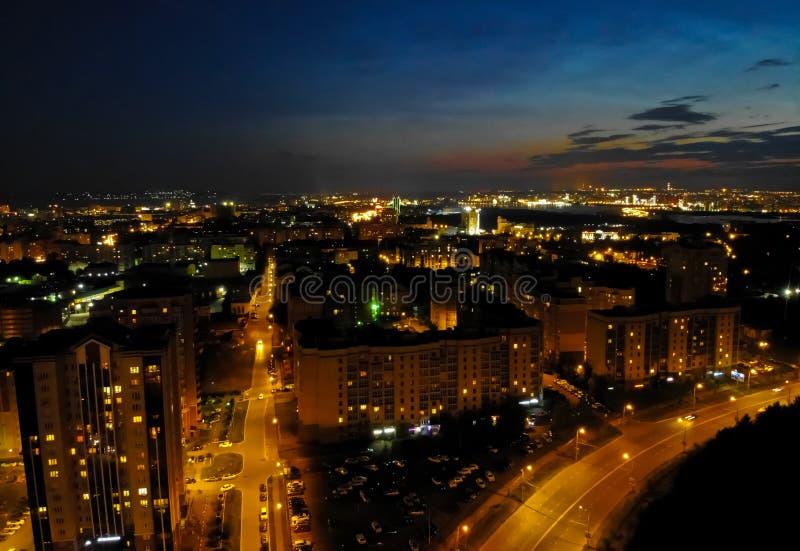 Flyg på surret ovanför nattstad med asfaltstadsvägar, bostads- byggnader och biltrafik på natten royaltyfria bilder