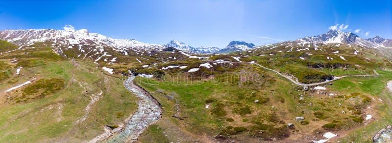 Flyg- panoramautsikt av maxima för högt berg i fjällängarna Ström som flödar under ängar i vårsäsong Idylliskt landskap, frikänd royaltyfri bild