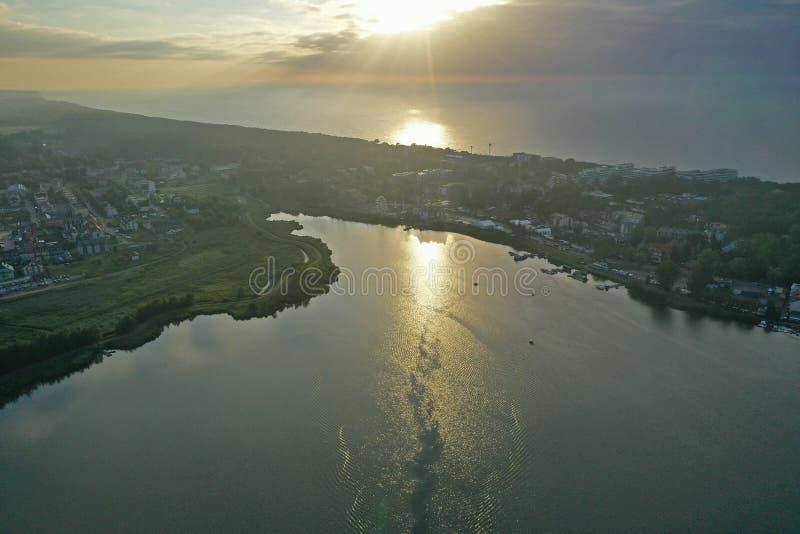 Flyg- perspektivsikt för surr på den Touristic staden som lokaliseras på spottat mellan havet och sjön under solnedgång royaltyfria foton