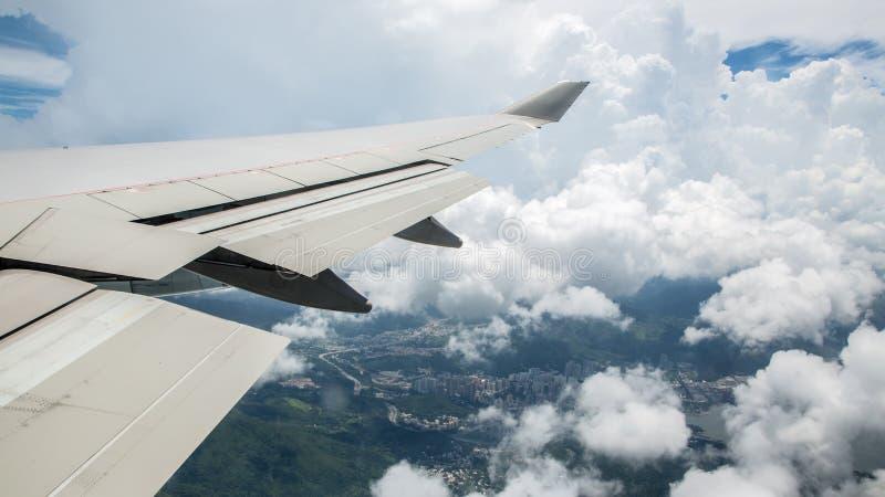 Flyg- resa Sikt till och med ett plant fönster av den Hong Kong staden med moln royaltyfria foton