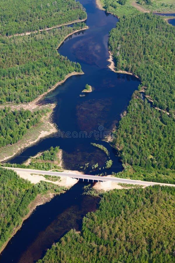 Flyg- sikt över bron på den lilla skogfloden royaltyfri foto