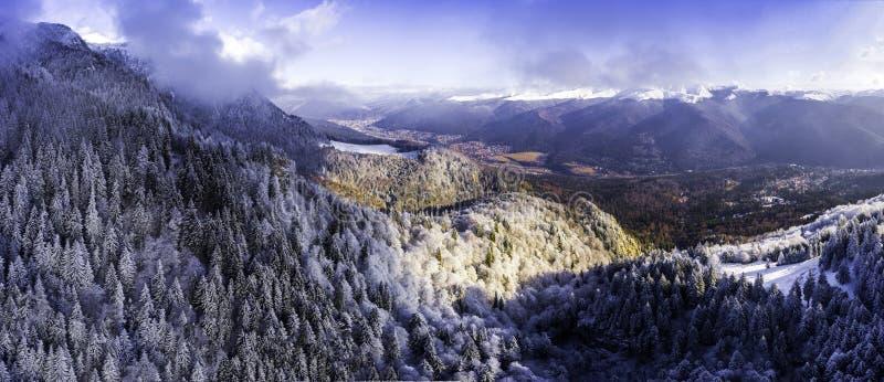 Flyg- sikt över den snöig bergkantdalen med moln, lyfta för kabelbil Transportatio för gondol för bergvinterskog turist- royaltyfria bilder