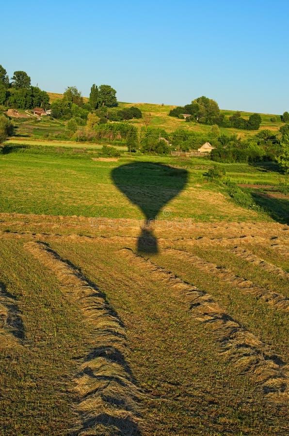 Flyg- sikt över fältet på en solig sommardag Ballongen för varm luft tog av från fältet i byn arkivfoton