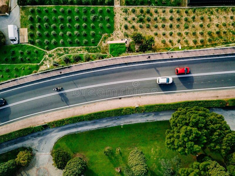 Flyg- sikt av asfaltvägen med bilar som går bland de jordbruks- fälten i Italien arkivfoton
