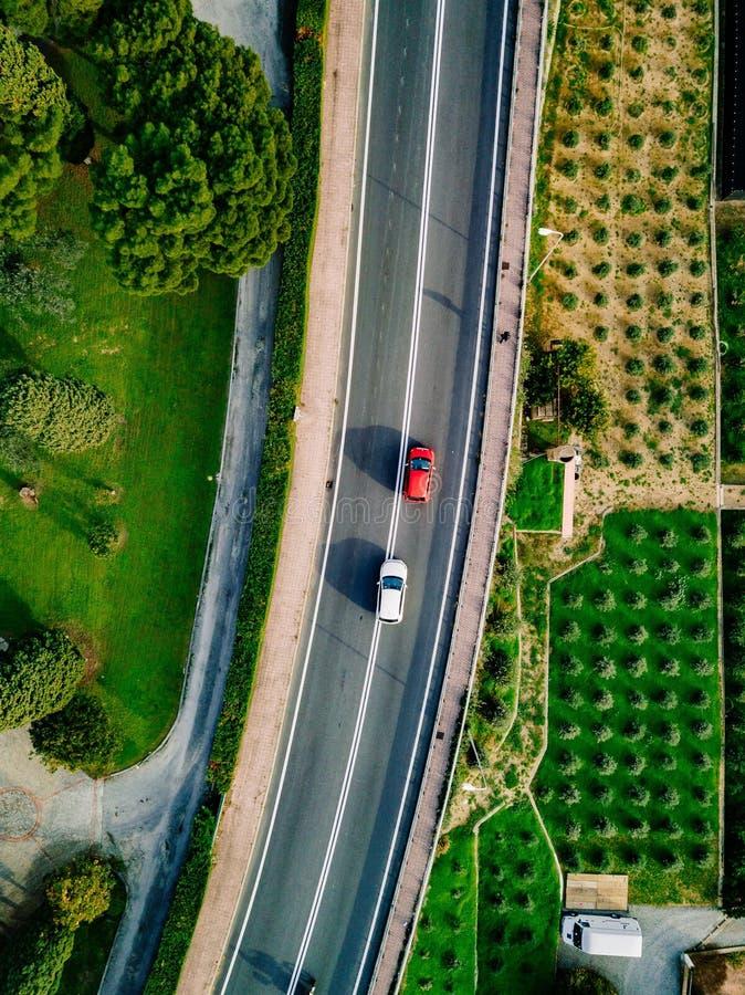 Flyg- sikt av asfaltvägen med bilar som går bland de jordbruks- fälten i Italien arkivfoto