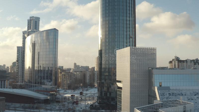 Flyg- sikt av att förbluffa futuristiska exponeringsglasskyskrapor i mitten av storstaden mot blå molnig himmel actinium modernt arkivfoton