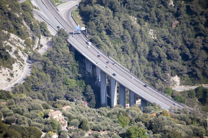 Flyg- sikt av biltrafik på en huvudvägbro med pelare och motorvägutgången arkivbild