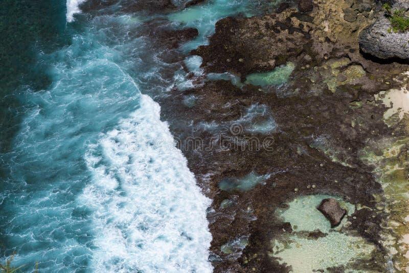 flyg- sikt av blåa havvågor som kraschar in i stenig kust fotografering för bildbyråer