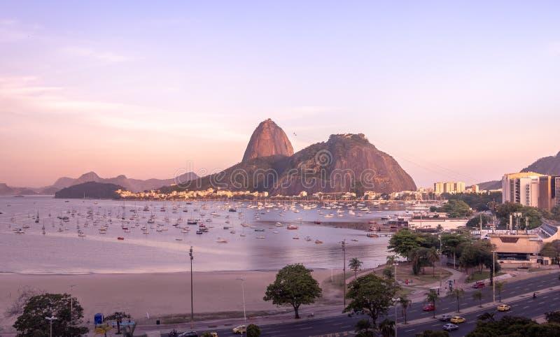 Flyg- sikt av Botafogo, den Guanabara fjärden och Sugar Loaf Mountain med en rosa solnedgång - Rio de Janeiro, Brasilien royaltyfri foto