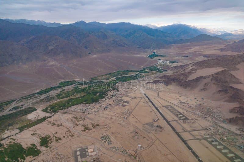 Flyg- sikt av bybosättningen med flygplatslandningsbanan i dalen som omges av berg arkivbild