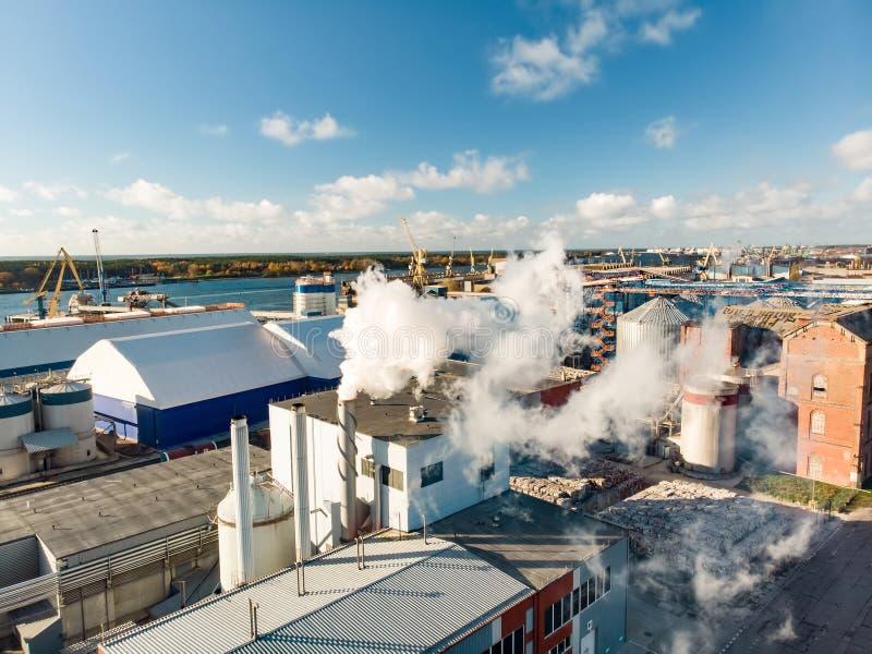 Flyg- sikt av byggnadskomplexet för pappers- och träbranschföretag under fungerande process resultera i intensiv vit dunst fotografering för bildbyråer