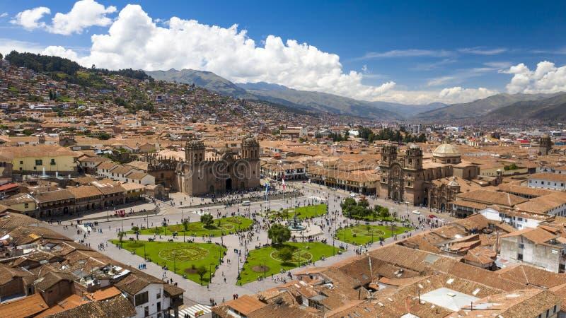 Flyg- sikt av Cusco'sens huvudsakliga plaza med folkmassan av folk som håller ögonen på flaggan lyfta handling arkivbild