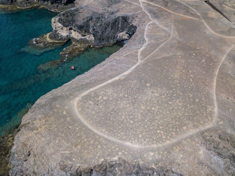 Flyg- sikt av de ojämna kusterna och stränderna av Lanzarote, Spanien, kanariefågel Röd jolle som förtöjas i en liten vik royaltyfri fotografi