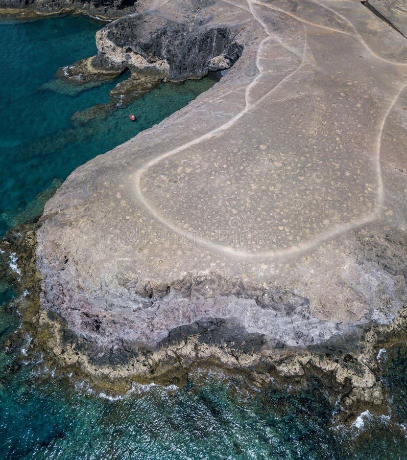Flyg- sikt av de ojämna kusterna och stränderna av Lanzarote, Spanien, kanariefågel Röd jolle som förtöjas i en liten vik royaltyfria foton