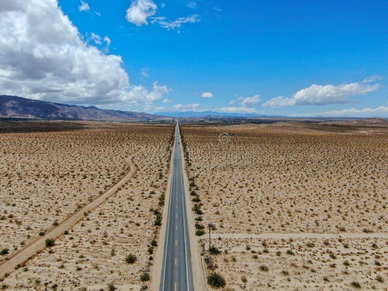 Flyg- sikt av den ändlösa raka vägen i öknen av Joshua Tree Park USA arkivfoton