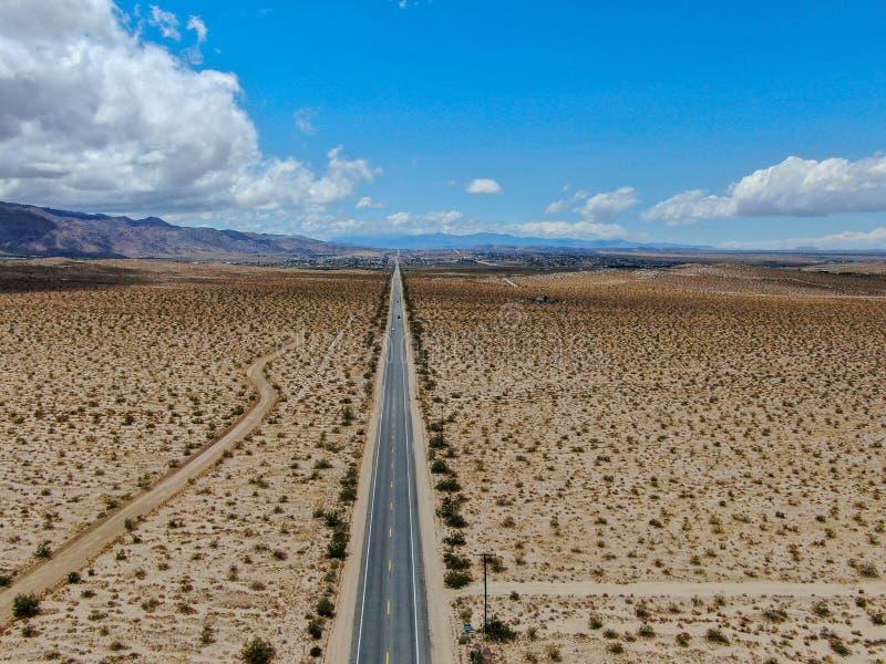 Flyg- sikt av den ändlösa raka vägen i öknen av Joshua Tree Park USA arkivbild