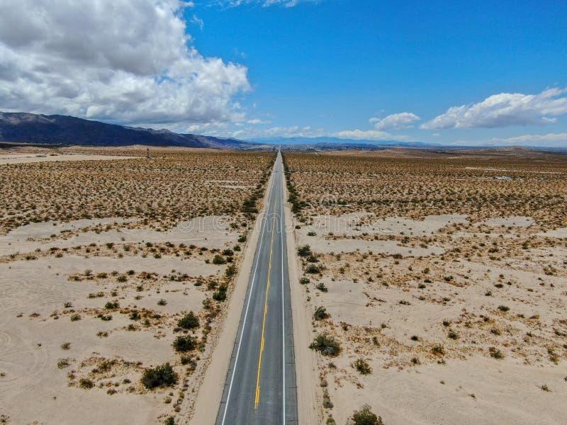Flyg- sikt av den ändlösa raka vägen i öknen av Joshua Tree Park USA royaltyfri bild
