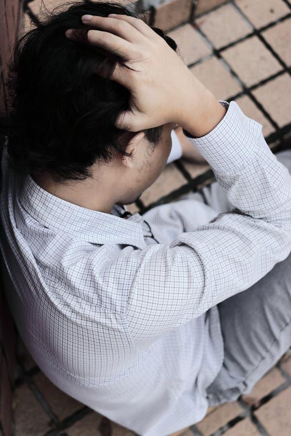 Flyg- sikt av den angelägna deprimerade unga asiatiska affärsmannen som sitter och trycker på pannan med händer fotografering för bildbyråer