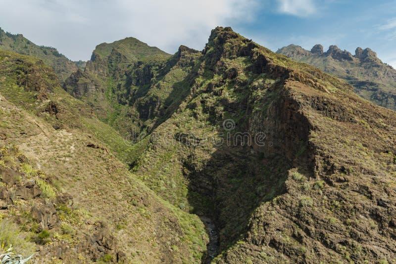 Flyg- sikt av den berömda helveteklyftan i Adeje solig dag Blå himmel och moln ovanför bergen Stenig spårande väg i torrt berg arkivbild