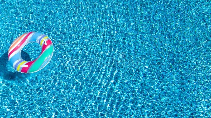 Flyg- sikt av den färgrika uppblåsbara cirkelmunkleksaken i simbassängvatten från över, semesterort för ferie för familjsemester royaltyfria bilder