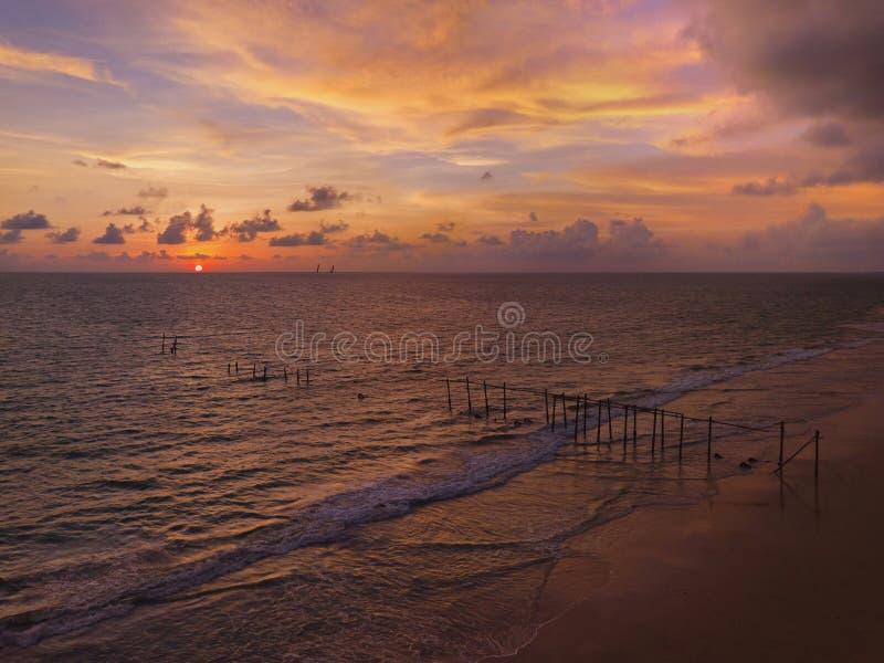 Flyg- sikt av den gamla träbro- och havsvågen på stranden på solnedgånghimmelbakgrund på Khao Pilai, Phangnga, Thailand Natur royaltyfria bilder