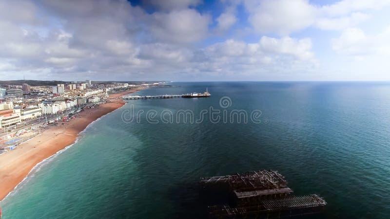 Flyg- sikt av den gamla västra pir och den nya Brighton Pier fotografering för bildbyråer