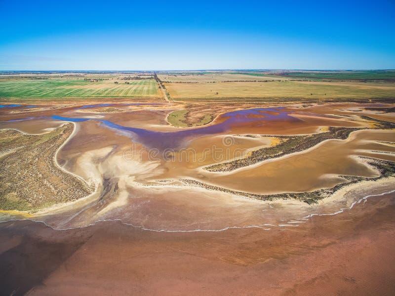 Flyg- sikt av den grunda salta sjön och jordbruksmarker arkivbild
