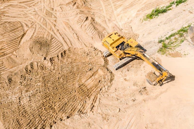 Flyg- sikt av den gula grävskopan på vägkonstruktionsplatsen fotografering för bildbyråer