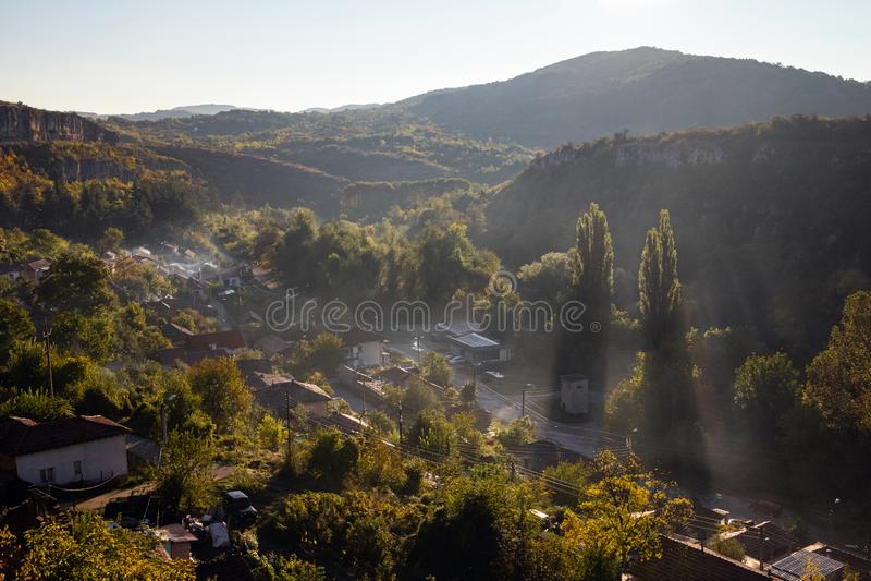 Flyg- sikt av den härliga dimmiga byn mellan berg i Lovech, Bulgarien Dimmig soluppgångsikt av stadsområdet som förbi omges royaltyfri fotografi