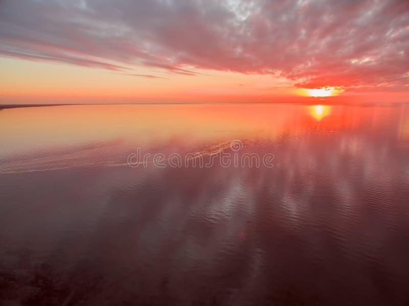 Flyg- sikt av den livliga röda och orange solnedgången som är hög ovanför havet inte arkivbilder